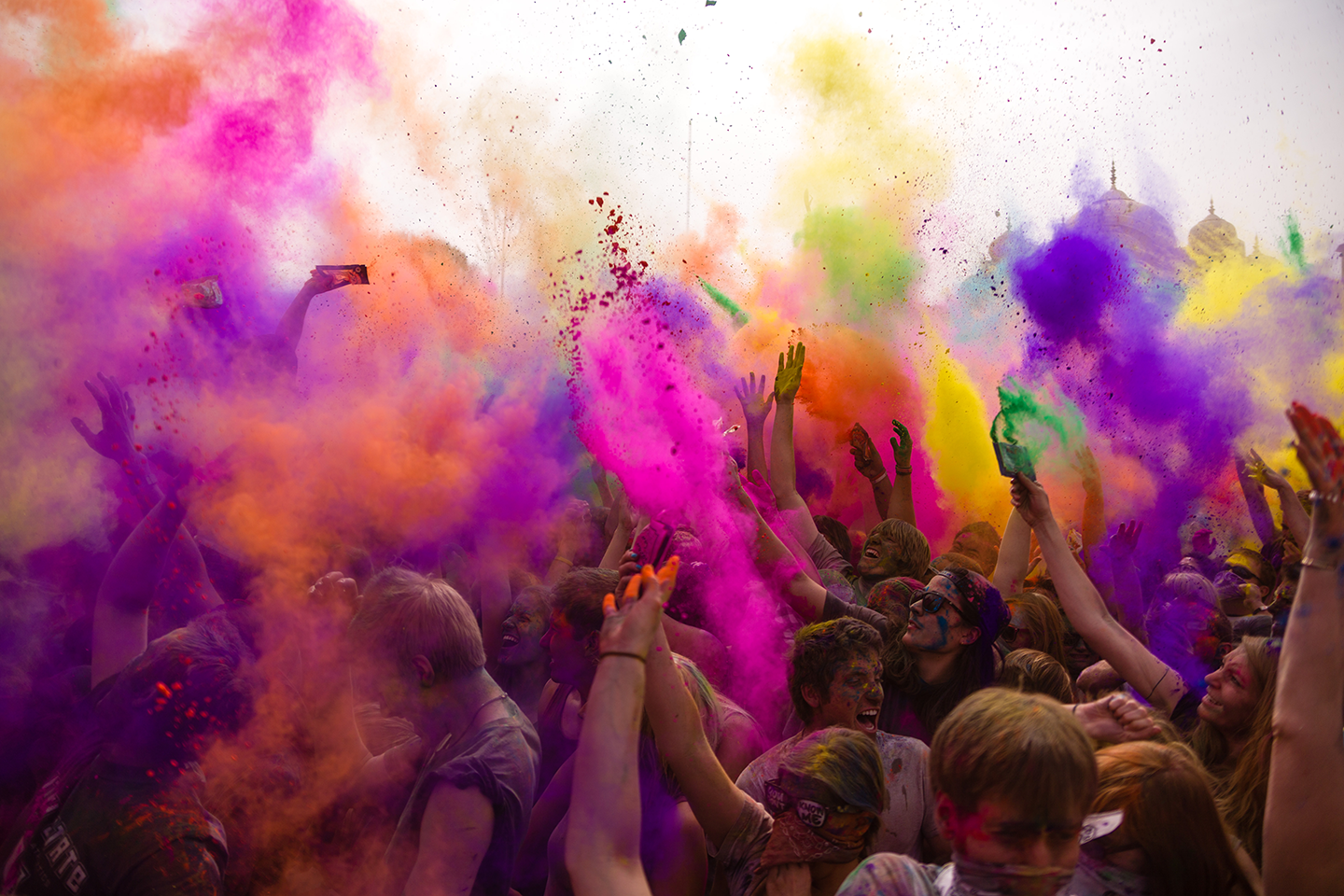 People throw colored powder into the air to celebrate the Holi Festival