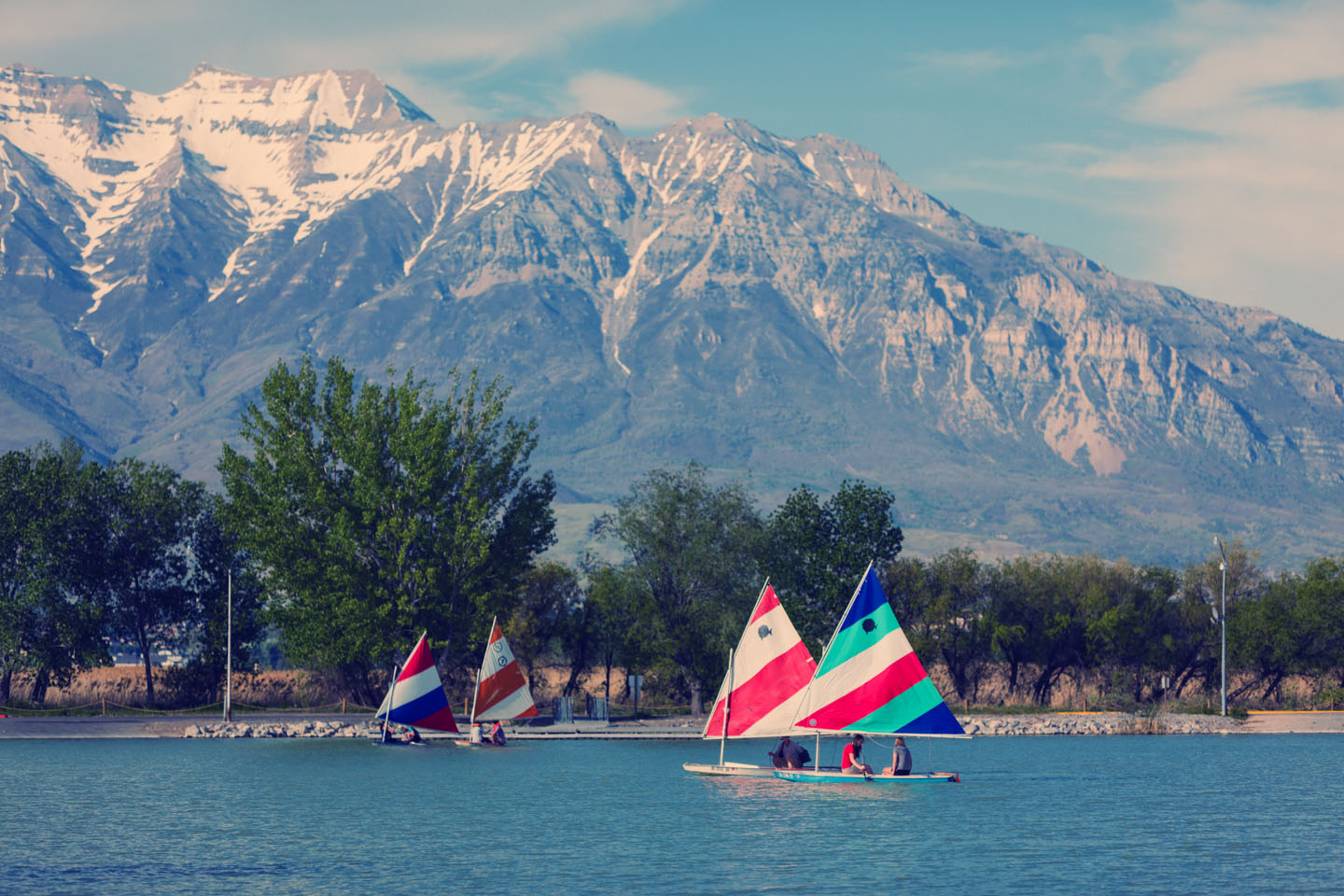 Timpanogos mountains in the background as people sail their boats