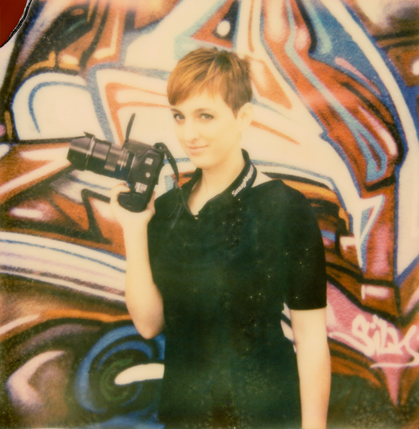 Pamela models her Canon 7D in front of a graffiti wall