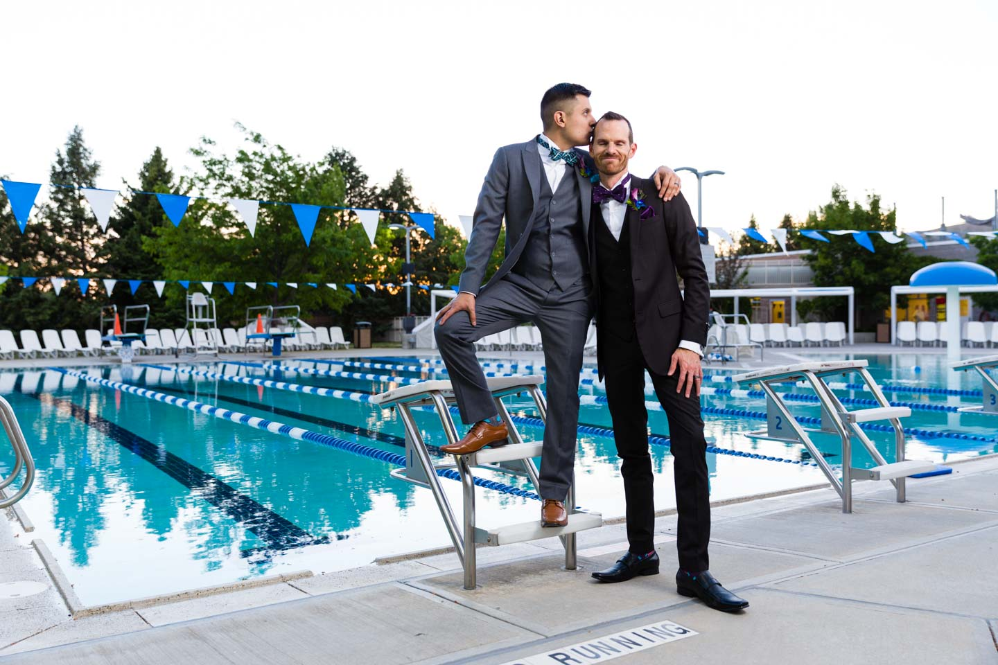 A tender moment for the grooms by the swimming pool