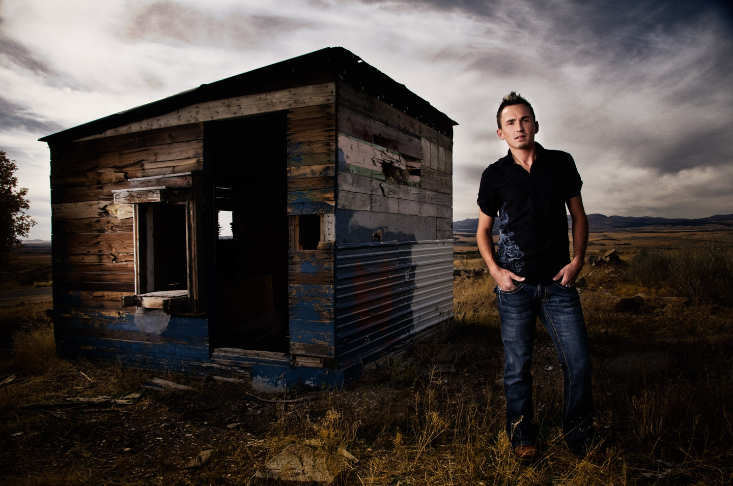 Stephen stands at a mini house at a ghost town