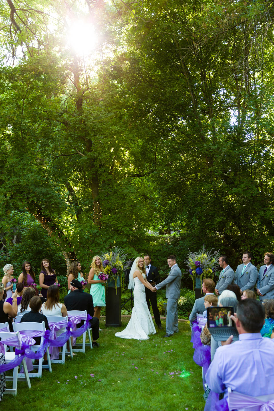 Sun shines through the trees of the backyard wedding ceremony