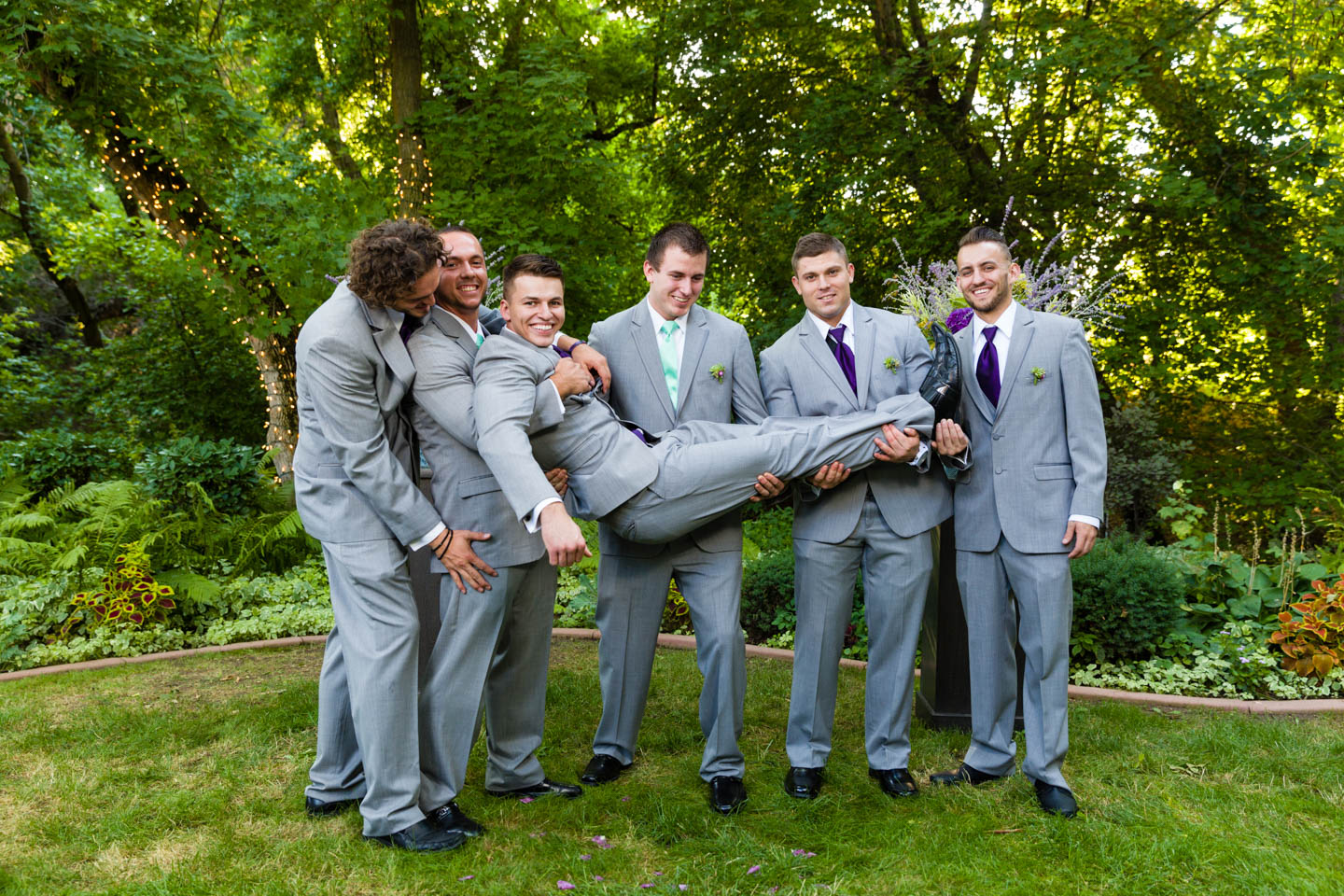 Groomsmen hold the groom for a fun shot