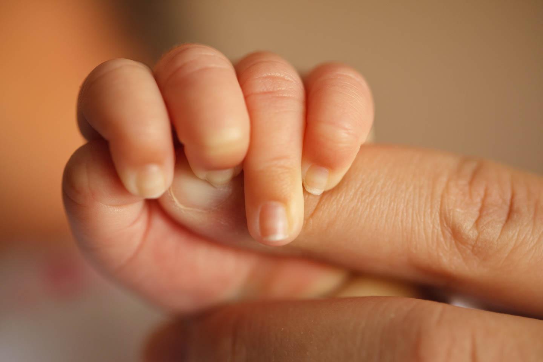 Sophie grabs her mom's finger
