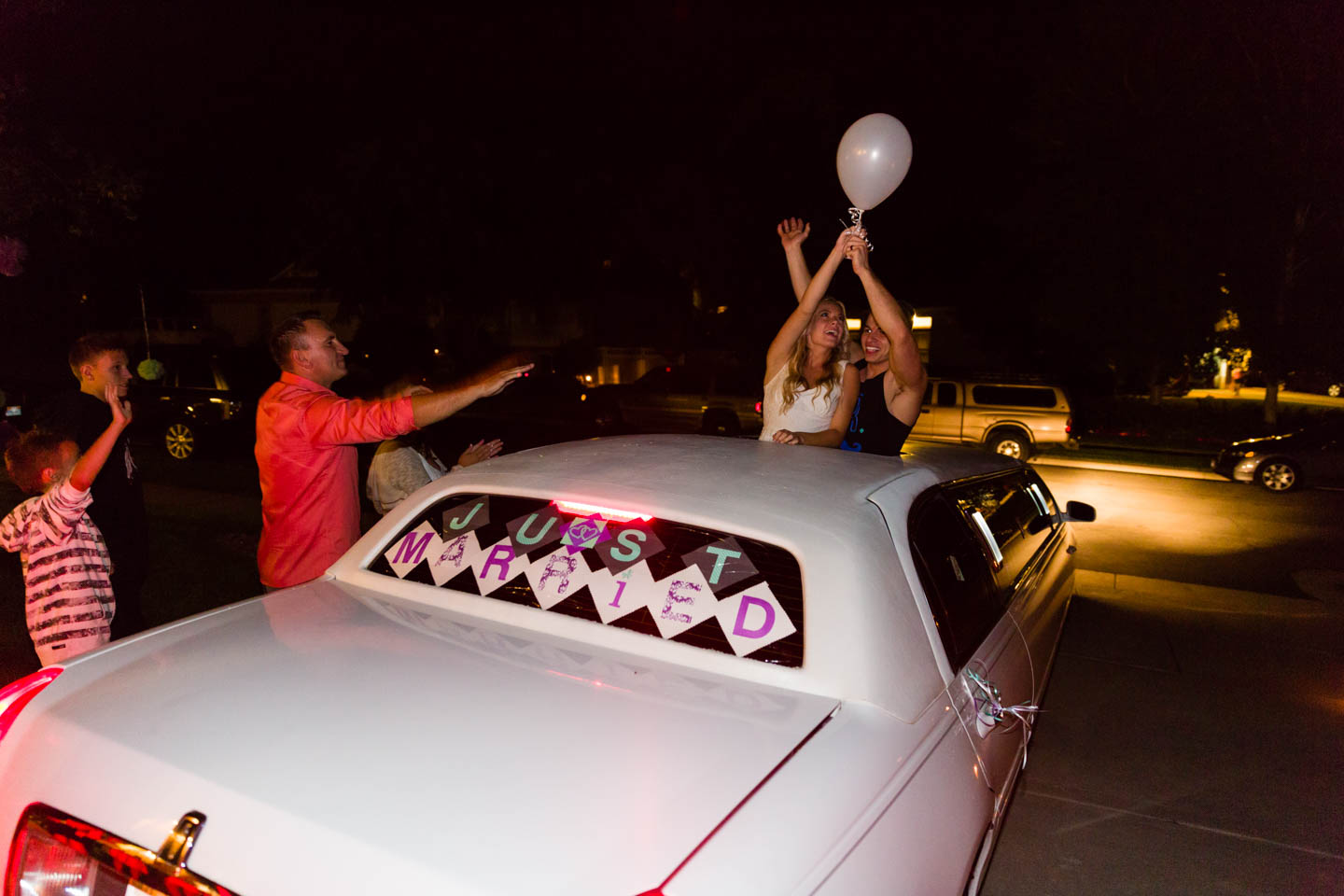 Wedding couple releases balloons from the limo