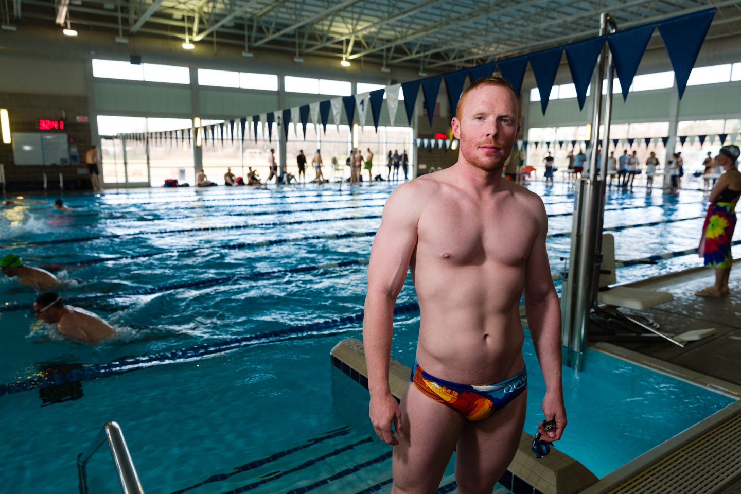 Male swimmer posing for the camera by the pool