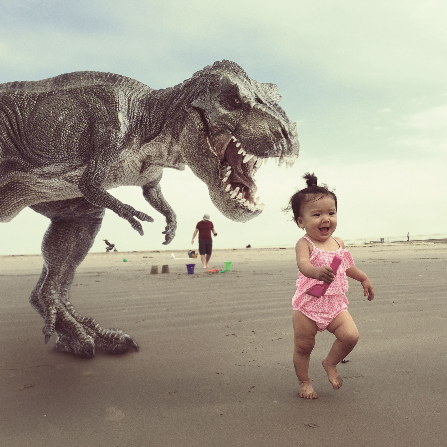 A tyrannosaurus rex chases after Olivia on the beach