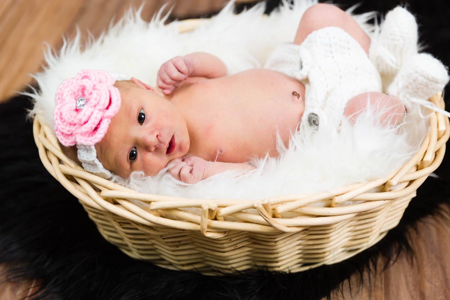 Newborn baby Harper in a basket and faux fur for decor