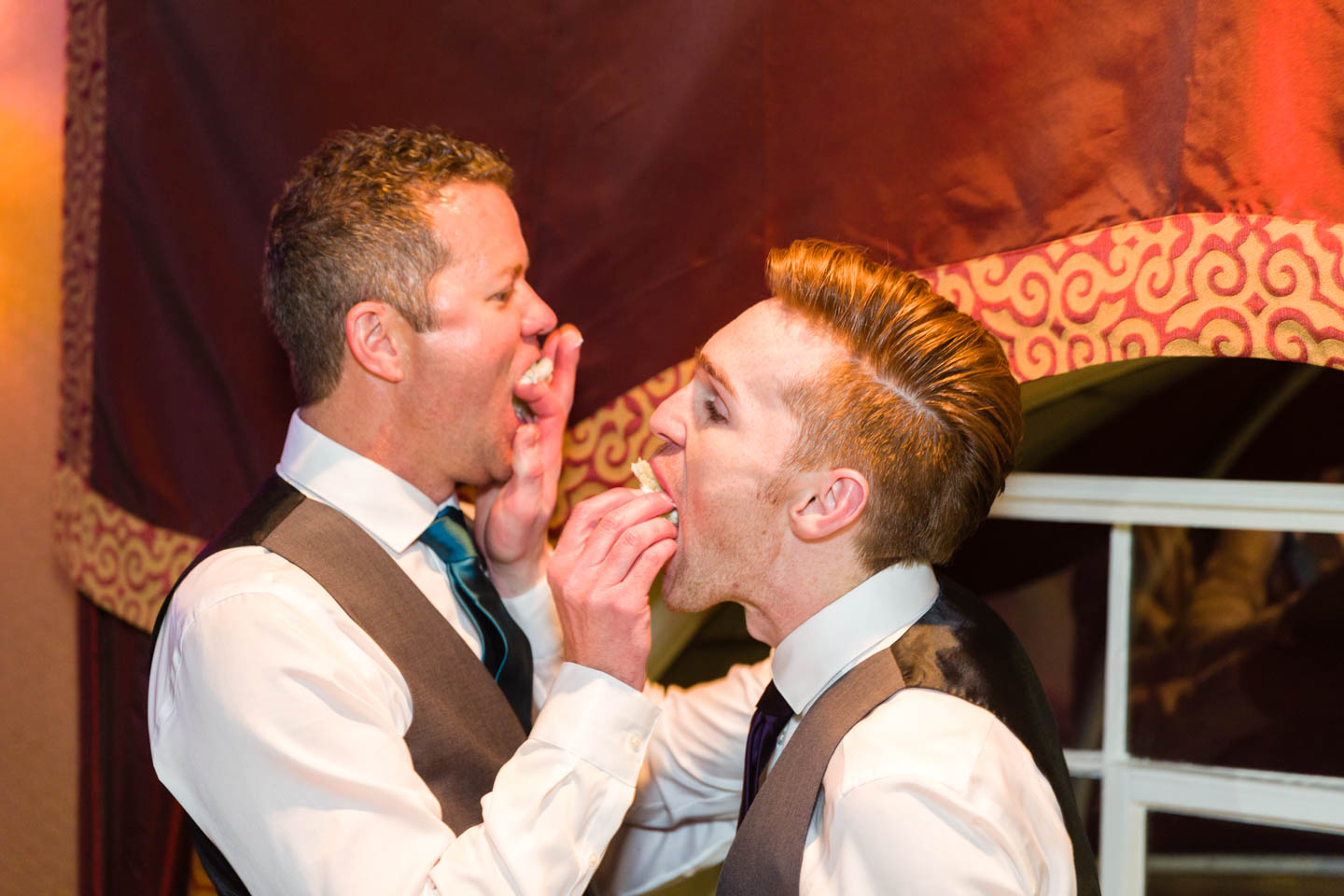 Grooms share wedding cake