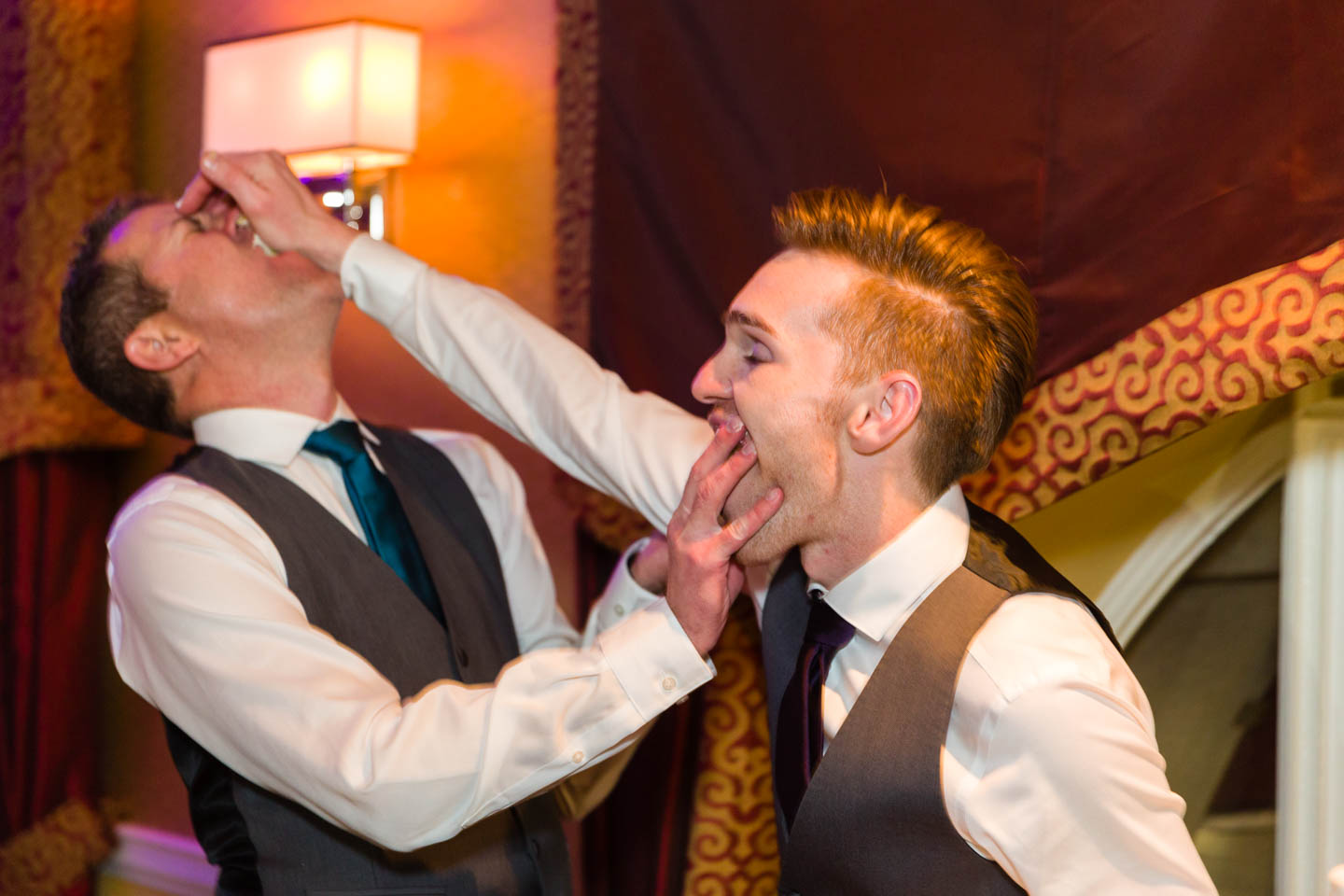 Grooms smash the wedding cake in each other's faces