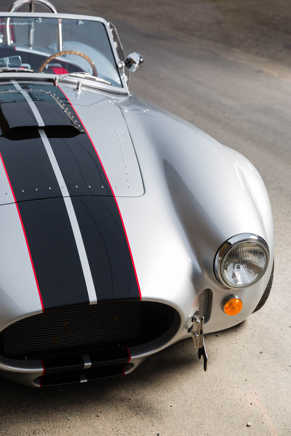 Photographing the curves of a silver Shelby Cobra