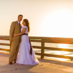 Wedding portrait on the pier overlooking the ocean and the setting sun