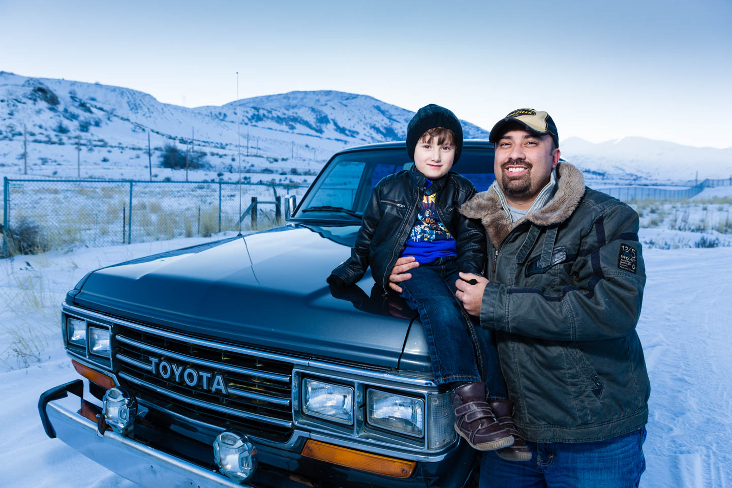 Luis poses with his son on the restored Land Cruiser