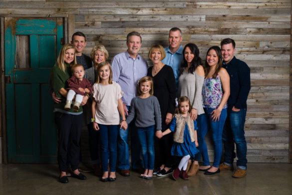 The whole family in front of a reclaimed wood barn