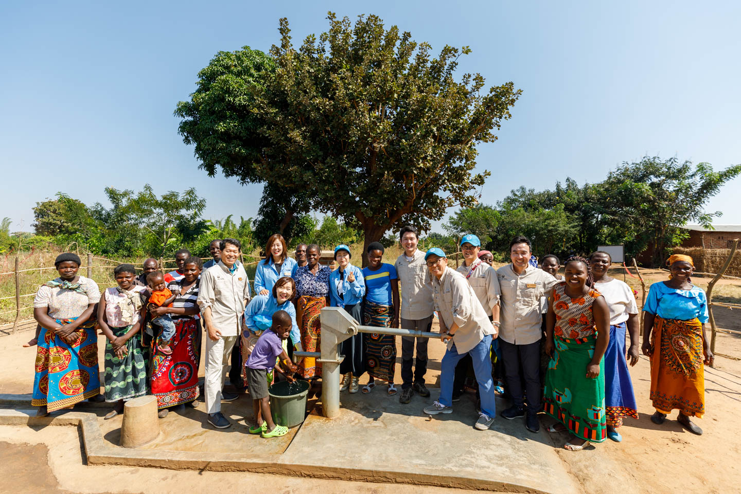 Korean distributors pose with the village. They had donated the well.