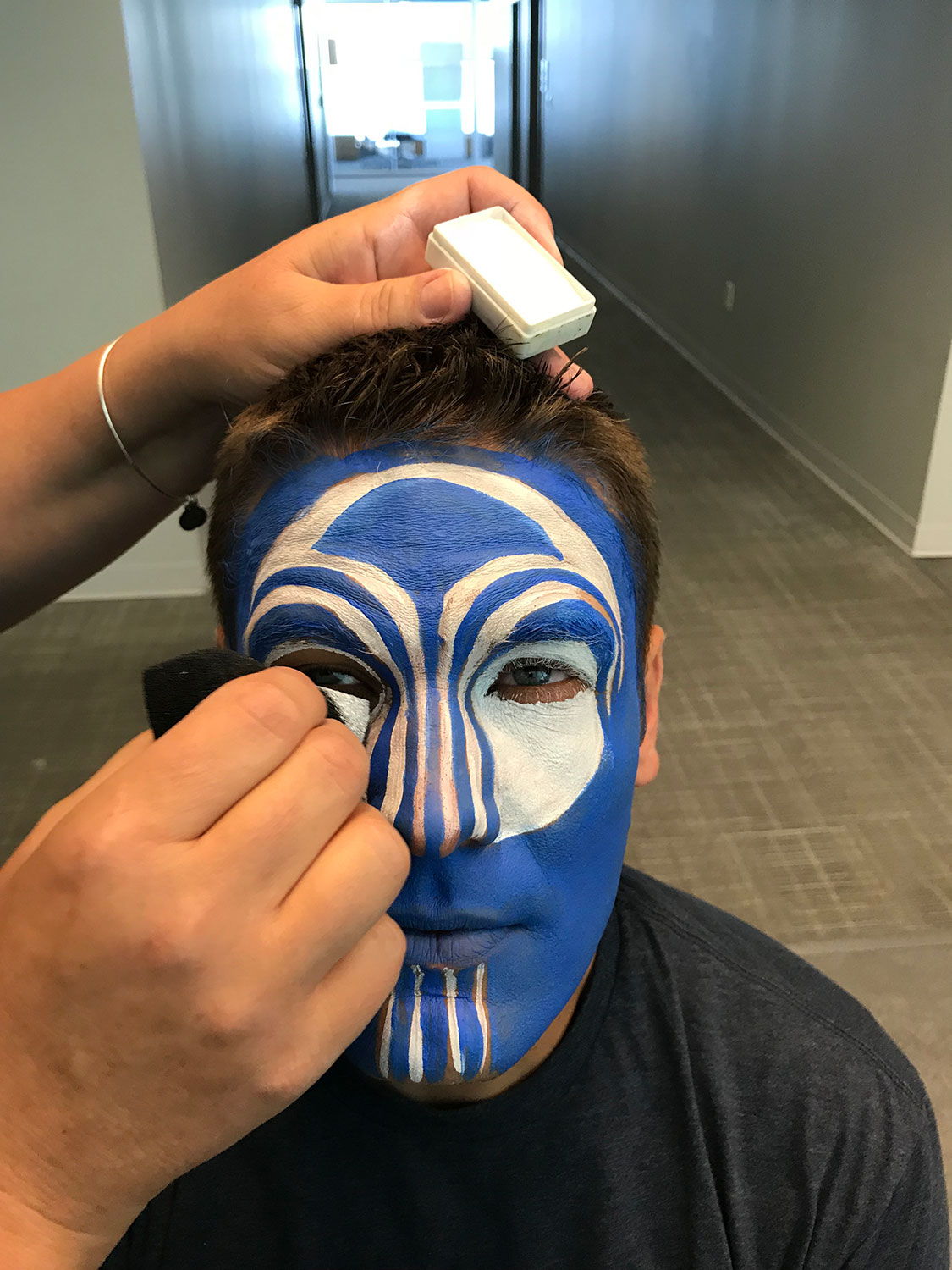 Face painting the Nu Skin logo
