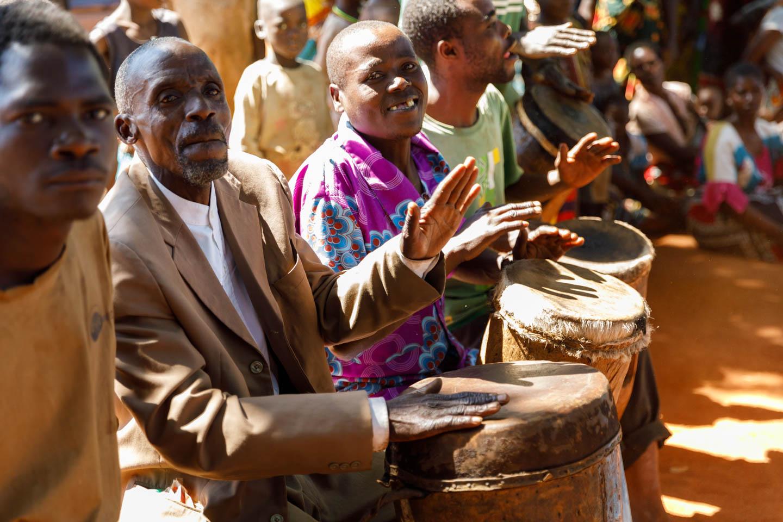 The village men drum the beat