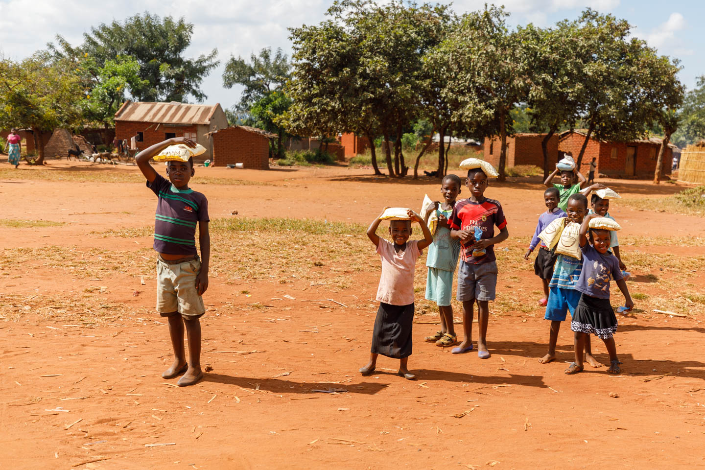 Malawian kids walk home with their new bags of VitaMeal