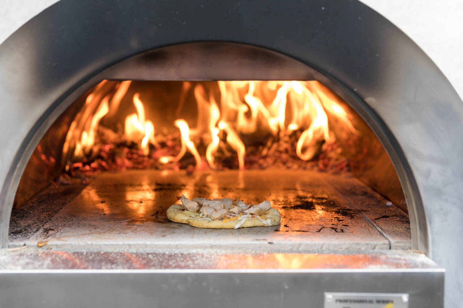 A pizza bakes in a wood fired oven—going Italian style